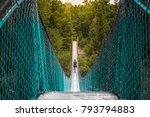 Woman crossing suspension bridge in Pinawa River Manitoba Canada