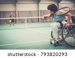 Small photo of Disabled mature woman on wheelchair playing tennis on tennis court.