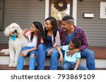 Stock photo family with children and pet dog sit on steps of home 793869109