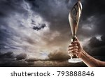 man's hand is holding gold cup...   Shutterstock . vector #793888846