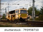 Small photo of Dolni Berkovice, Czech Republic - September 15, 2017 - Yellow railroad appliance on track, industrial area. Working train MTH Pilsen - track tamping unit (tamper, packing machine) Plasser und Theuer.