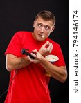 Small photo of A cowardly guy frightenedly holding a game joystick and eating tasty popcorn. On a black background.