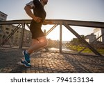 young sporty man jogging across ... | Shutterstock . vector #794153134