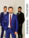 Small photo of Businessmen wear smart suits and ties. Business, leadership and compromise concept. Executives express confidence and hold hands in pockets on light grey background. Men with beard and confident faces