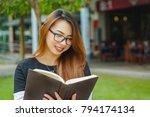 a girl in a park holding a book | Shutterstock . vector #794174134