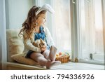 Stock photo cute happy little child girl is wearing bunny ears on easter day sitting on window sill holding her 794336926