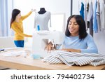 Small photo of Attentive colleagues. Reliable skilled cheerful tailor sewing and feeling glad while her friendly responsible colleague standing behind her and measuring a new striped blouse on a mannequin
