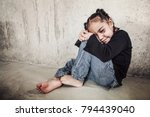 Small photo of Abused child with eyes closed hiding next to a wall