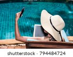 Portrait Beautiful Woman smile Sitting in deck chair and using mobile smart phone for Selfie near swimming pool in vacation time blue water