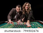 Man with woman playing roulette at the casino. Addiction to the  - stock photo