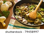 closeup of mushrooms and onions in pan and mixed with wooden spoon - stock photo