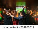Stock photo friends watches football on tv in a sport bar 794835619