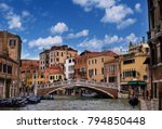 Small photo of Venice, Italy - 9 October 2013: beautiful typical view of the Venice canal with tourists passing over bridge, on a fine sunny day with blue sky and clouds, charms and splendor of this eternal city