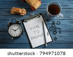 Small photo of Composition with clock, toy cars and phrase TIME TO ENGAGE written on clipboard