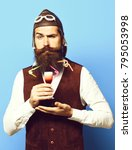 Small photo of handsome bearded pilot or aviator man with long beard and mustache on funny face holding glass of alcoholic shot in vintage suede leather waistcoat with hat and glasses on blue studio background