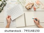 Small photo of Wedding background with checklist and calendar. Female hands arranging marriage, filling in planners on white wooden table with lots of tender bridal stuff, top view