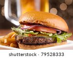 gourmet cheeseburger with mug of beer in background - stock photo