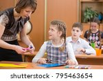 Small photo of School children working at labour lesson. Teacher helping pupil.