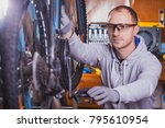 handsome bicycle mechanic doing ... | Shutterstock . vector #795610954