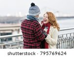Small photo of Man in winter knitted hat makes funny rude women in red scurf. Guy in red jacket care about lady. Women happy to meet men.
