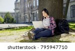 Small photo of College student sitting under tree in campus, using laptop, writing final paper