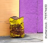Small photo of This old yellow trash can, made of metal and beat up looks amazing against the purple and peach walls of an old boardwalk midway. It leaves a color blocking pattern in this square image.