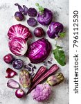 Small photo of Raw purple vegetables over gray concrete background. Cabbage, radicchio salad, kohlrabi, carrot, cauliflower, onions, artichoke, beans, potato, plums. Top view, flat lay.