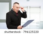 surprised businessman reading a ... | Shutterstock . vector #796125220