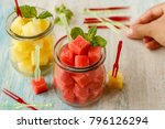 Small photo of Cut cubes of red and yellow watermelon in glass jars with mint and canape picks over white and blue washed wooden table. Woman's hand taking a pick. Side view.