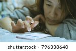 woman using cellphone in bed | Shutterstock . vector #796338640