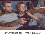 tattooed couple with remote... | Shutterstock . vector #796418110
