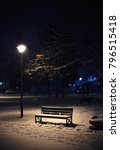Small photo of A night scene from a city park, a view of the bench, a lampion, and snow-covered branches.