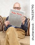 Small photo of A man wearing glasses is sitting on a couch at home, reading a newspaper reporting fake news. Fake Lorem ipsum text.