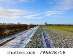 A Straight Snowy Farm Road Wit...