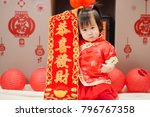 "Small photo of Chinese baby girl traditional dressing up with a ""Gong Xi Fa Cha"" scrolls means ""wishing you enlarge your wealth"" some ""FU"" mean ""lucky""greeting card on the wall"