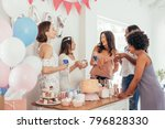 Stock photo pregnant woman celebrating baby shower party with female friends at home group of multi ethnic 796828330