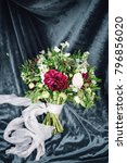 Small photo of Bouquet of marsala and white flowers with greenery decorated by ribbons, laying on velour cloth