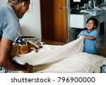 dad and son changing bed sheet... | Shutterstock . vector #796900000