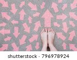 Small photo of Pink Arrow Choice Concept. Female Bare Feet with Pink Nail Polish Manicure Standing and Many Direction Arrows Choices on the Road Background Great for Any Use.
