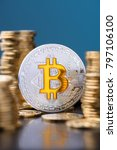 Small photo of Bitcoin. Bitcoin coin bit golden bit sybmol logo with gold coins stacks vertical on blue background with reflection.