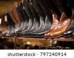Side perspective a pair of brown alligator leather cowboy boots, on a row of other boots