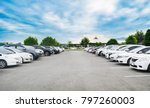 Car parking in large asphalt parking lot with trees, white cloud and blue sky background in front of hall building. Outdoor parking lot with fresh ozone and green environment concept