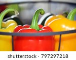 Small photo of Hanging basket with several sweet peppers with focus on the red one as symbol for healthy and adequate nutrition