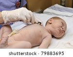 A newborn baby gets a lung examination by a nurse with stethoscope. - stock photo