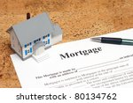 A conceptual image of a scale house and mortgage forms for the people buying a house. - stock photo
