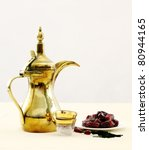 A traditional Arabian coffee pot with glass coffee cups a tray of dates and a set of prayer beads. Coffee and dates are often eaten at the end of the fasting period in Ramadan - stock photo