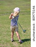 little girl hitting golf balls - stock photo