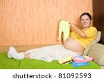 pregnant woman with baby's clothes  on sofa - stock photo