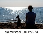 Stock photo girl silhouette sitting on the beach with a small dog 81192073