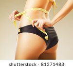 slimming woman in panties with yellow measure - stock photo